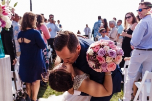 wedding coordination by magical moments by megan, bride and groom kissing at end of the aisle, beautiful pink and purple floral bouquet, beach wedding ceremony, venue scripps seaside forum, Cerritos Wedding Planner, San Diego Wedding Planner, Orange County Wedding Planner, Los Angeles Wedding Planner